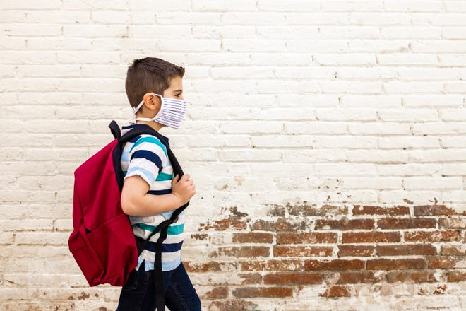 A boy going to school with protective mask