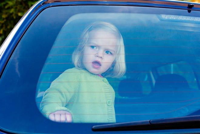 A girl is closed in the back of a car on a hot day.