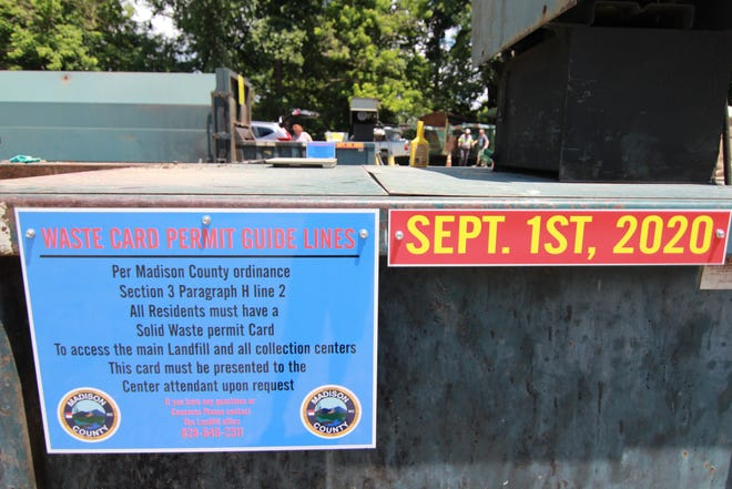 Signs at the Marshall collection center educate residents about a coming policy requiring individuals to show their solid waste permit cards when using county trash facilities.