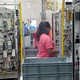 An employee works behind plexiglass at DENSO