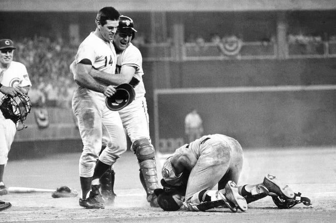 National League's Pete Rose, left, is hugged by his teammate Dick Dietz while American League's catcher Ray Fosse lies injured on the ground, after Rose crashed into him to score the game-winning run for the National League team, in the 1970 All-Star Game, in Cincinnati, Ohio, July 14, 1970. Fosse suffered a fractured shoulder in the collision.