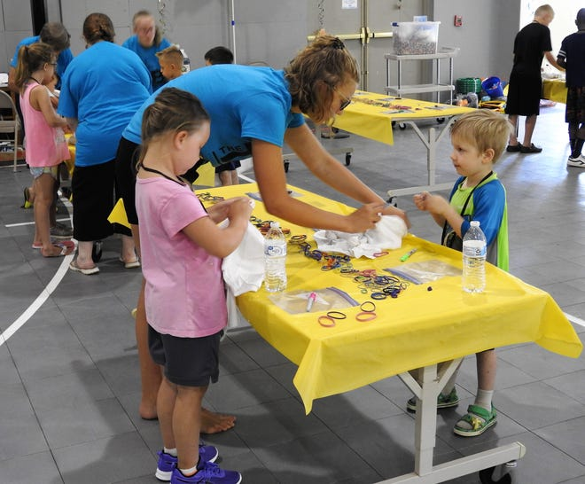 Anna Janson helps Kayleen Stocker, 6, and Valaric Loper, 5 prepare T-shirts to be tie-dyed during a vacation Bible school at Coshocton Christian Tabernacle. Different from years past, the church held two separate days for different age groups and practiced health checks and hand washing.