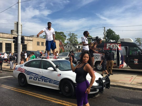 Members of a crowd protesting a fatal Detroit police shooting jump onto a squad car.