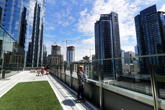 Connie Wade, center, looks out over the growing skyline of downtown Seattle, Wednesday, June 17, 2020, as she stands in an outdoor deck area at Mary's Place, a family homeless shelter located inside an Amazon corporate building on the tech giant's Seattle campus.