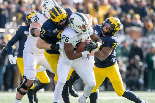 Michigan State running back Brandon Wright is tackled for a loss by Michigan defensive lineman Aidan Hutchinson, left, and linebacker Khaleke Hudson in the 2019 game in Ann Arbor.