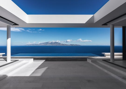 An outdoor terrace culminating in an infinity pool frames a remarkable view of Cephalonia and the broad blue expanse of the Ionian Sea.