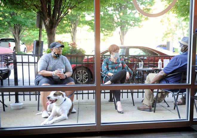 From left: Debbie Calhoun with dog Bronx, Kaitlin Moore and Mike Webster enjoy cool brews on the patio at Myriad Brewing Company at on Thursday, July 9, 2020.