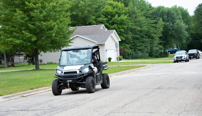 Jason Sandberg takes a ride with his four-wheeler near his home on Sixth Street in Oconto on July 9.