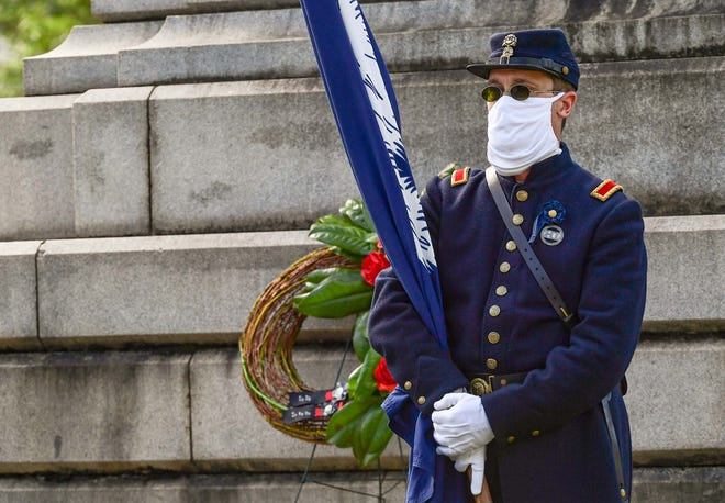 A man dressed with the South Carolina Memorial Honour Guard holds a State flag near the Confederate monument on the grounds of the Statehouse on the five-year anniversary of the removal of the Confederate flag from the Statehouse grounds in Columbia, S.C. Friday, July 10, 2020.