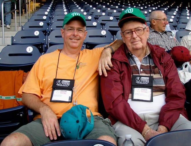Chuck and Charlie Stinnett pose in the grandstand at Washington Nationals Park before a Nationals-New York Mets game on Sept. 17, 2008 during a chartered baseball bus trip in the Northeast. They're wearing green caps that were handed out as part of a celebration of Halfway to St. Patrick's Day six months before that traditional Irish holiday.