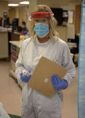 Nurses wear personal protective equipment when handling samples in labs to slow the potential for COVID's spread inside Jackson-Madison County General  Hospital.