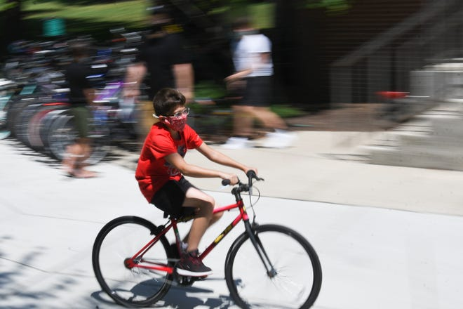 Antonio Romero, 11, of Lansing, tests a used bike on Thursday, July 9, 2020, outside of the MSU Bikes Service Center. He was shopping with his brothers, dad and grandma. He left the store with new wheels.