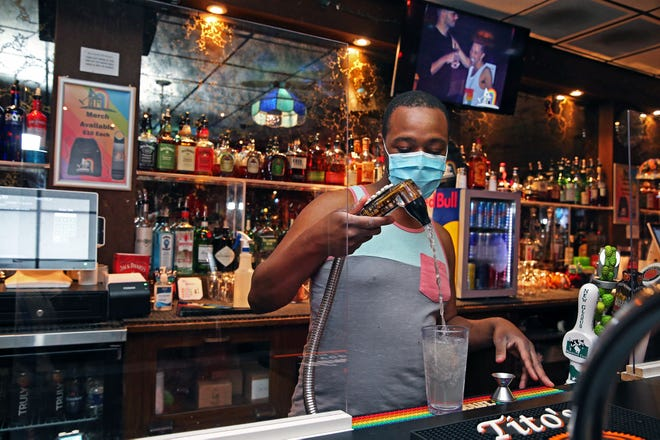 Bartender Ray McGee wears a mask while working at This Is It! at 418 E. Wells St. on Wednesday, July 8, 2020. Also added at the bar are plexiglass windows as restaurant owners start their reopening during the coronavirus pandemic. This Is It! requires all those entering their bar to wear a mask. Patrons must also have their temperature taken upon entering as well.