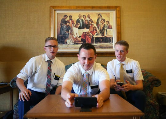 The Church of Jesus Christ of Latter-day Saints missionaries Elder Nathan Bohman (left), Elder Reese Stoddard (center) and Elder Daniel Sumsion hold a video chat at their church in Mesa on June 30, 2020. Instead of bikes, the COVID-19 pandemic has forced them to perform their work remotely using phones.