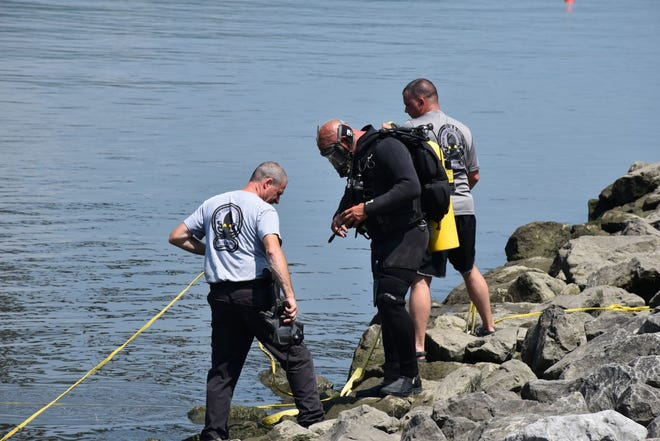 Police officers respond after a car was found in the Hudson River. The vehicle was later found to contain human remains.
