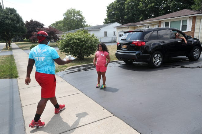 Brandon Gamble, a Foodlink intern, delivers a meal to a child on Abbott Street.