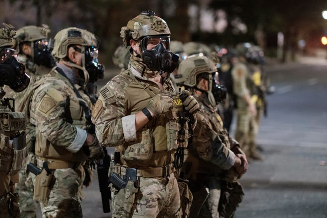In this photo provided by Doug Brown, agents from different components of the Department of Homeland Security are deployed to protect a federal courthouse in Portland, Ore., Sunday, July 5, 2020.