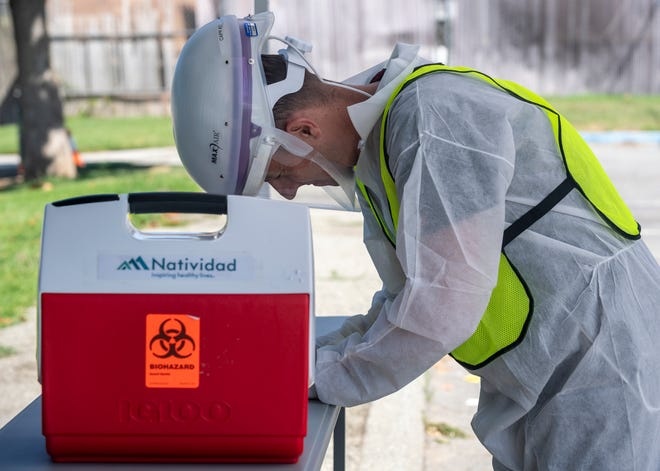 Christopher Henderson, writes down information after performing a COVID-19 test in King City, Calif., on Thursday, July 9, 2020.