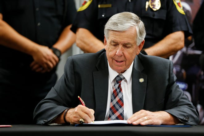 Missouri Governor Mike Parson signs a bill into law at the Springfield Regional Police and Fire Training Center on July 10, 2020. Parson issued four vetoes and signed Sen. Lincoln Hough's bill creating a fund for firefighters with cancer last week.