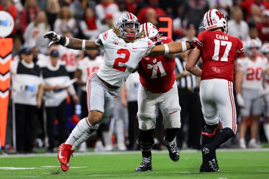 Former Ohio State Buckeyes defensive end Chase Young (2) grabs onto the jersey of Wisconsin Badgers quarterback Jack Coan (17) during the 2019 Big Ten Championship.