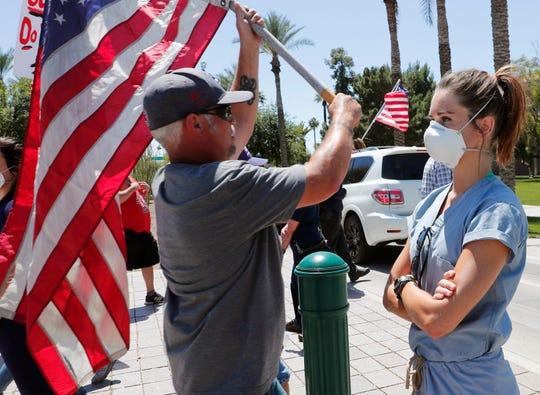 Un hombre protesta en contra del confinamiento, en el Capitolio de Arizona.