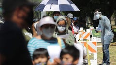 A COVID-19 testing associate dressed in personal protective equipment (PPE) assists people waiting in line at a testing center at Lincoln Park amid the coronavirus pandemic on July 07, 2020 in Los Angeles, California.