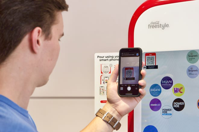 Consumers can hold their camera up to the display, which will auto-scan a QR code and connects to the cloud to bring the Coca-Cola Freestyle user interface to their phone.