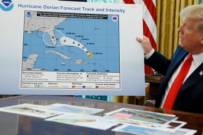 In this Sept. 4, 2019, file photo, President Donald Trump holds a chart as he talks with reporters after receiving a briefing on Hurricane Dorian in the Oval Office of the White House in Washington.