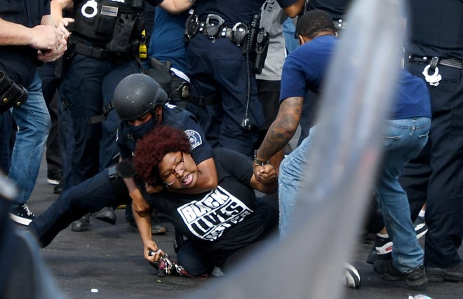 Detroit Will Breathe organizer Nakia Wallace is taken down and arrested by Detroit Police Department officers during a protest on West McNichols Road at San Juan Drive in Detroit on July 10, 2020. An officer appears to have their arm wrapped around her neck during the arrest. Wallace was released from jail the next morning.