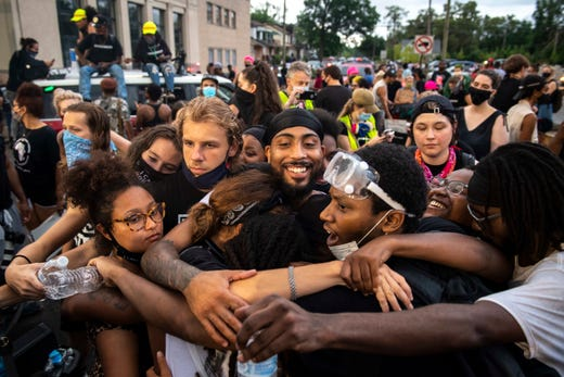 Protesters embrace each other at the intersection of San Juan Drive and West McNichols Road at the end of the protest.