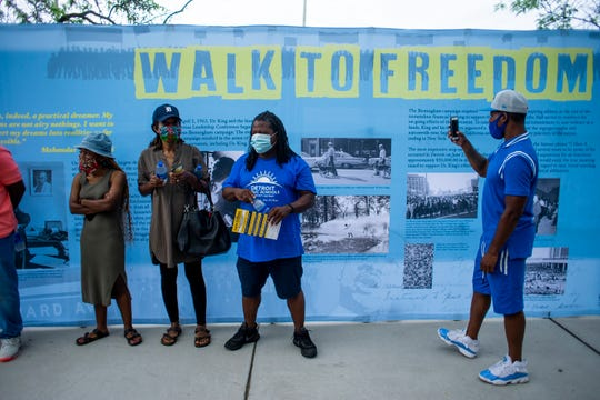 People stand in front of the Charles H Wright museum's Walk to Freedom portable exhibition at the 7th Annual Occupy the Corner event.