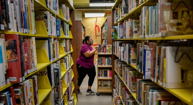 Library employee Carla Bradley pushes a cart full of books during the move into the new $8.4 million expansion at the Henderson County Public Library Thursday, July 9, 2020.