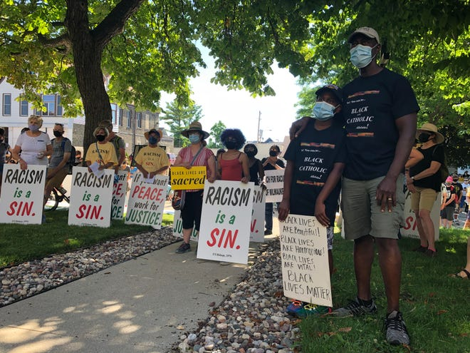 Carl Carby, right, and his son, London, join protesters outside St. Francis of Assisi Catholic Church in Milwaukee Saturday for a march for racial justice organized by the Archdiocese of Milwaukee's Black Catholic Ministry Commission.
