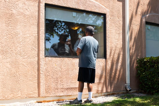 A resident at the rehabilitation center chats with a relative through a window, as a health care worker looks on.
