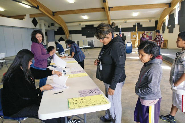 Voters check in on Aug. 26, 2014 as they prepare to cast their ballots in the Navajo Nation primary election at the Nenahnezad Chapter House in Nenahnezad.