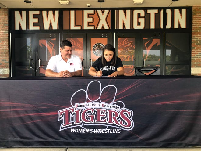 New Lexington senior Leilah Castro, the Muskingum Valley League's first female state wrestling champion, signs her national letter of intent with Campbellsville (Kentucky) University on Friday at the high school. Also pictured is Campbellsville head coach Lee Miracle, who has coached 12 national champions in the last five seasons.