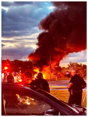At the scene of the tanker crash and fire, a driver is stopped and questioned by Bloomfield Township police.