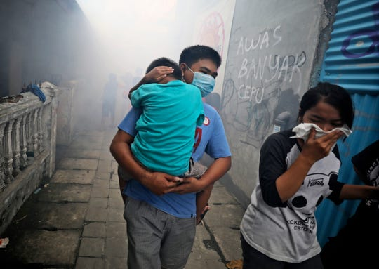 People move away as health workers fumigate a slum to prevent an outbreak of dengue fever in Jakarta, Indonesia, on Monday, March 23, 2020.
