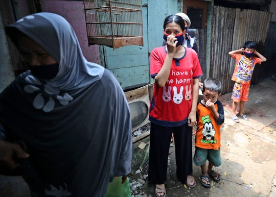 People cover their nose and mouth as workers fumigate their neighborhood to prevent a dengue fever outbreak in a slum in Jakarta, Indonesia, Wednesday, April 22, 2020.