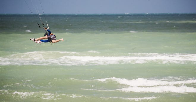 Fort Myers resident Jackson Trescott catches air and waves while kiteboarding at Blind Pass at the bridge that connects Sanibel and Captiva on Sunday, July 12, 2020.