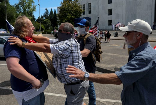 """A pro-police supporter pushes a """"Black Lives Matter too"""" supporter during the Back the Blue rally at the Oregon State Capitol, in Salem, Oregon, on Saturday, July 11, 2020. The Black Lives Matter too supporter was not affiliated with either group that had gathered at the Capitol."""