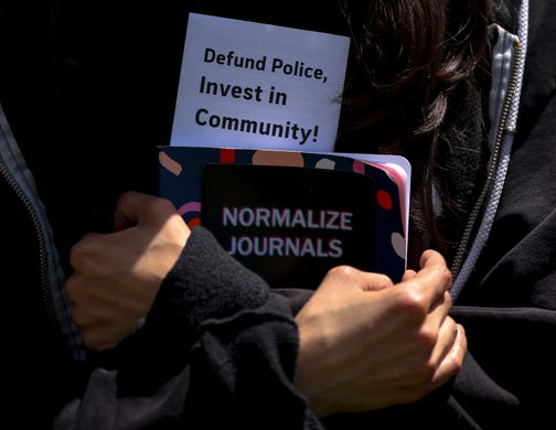 Nayeli Cruz clutches a journal while listening to speakers during the War on Racism rally at the Oregon State Capitol, in Salem, Oregon, on Saturday, July 11, 2020.