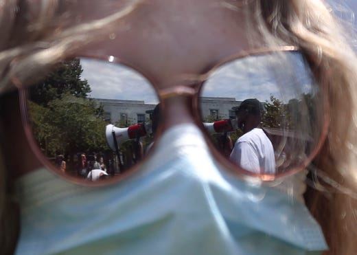 A reflection of William Jones is seen in Shea Weiner's glasses during the War on Racism rally at the Oregon State Capitol, in Salem, Oregon, on Saturday, July 11, 2020.