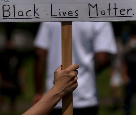 A demonstrator holds a sign during the War on Racism rally at the Oregon State Capitol, in Salem, Oregon, on Saturday, July 11, 2020.
