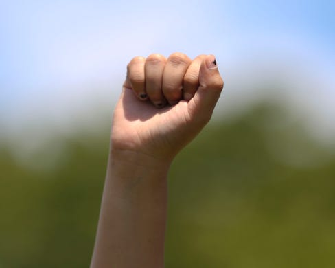 A demonstrators raises a fist during the War on Racism rally at the Oregon State Capitol, in Salem, Oregon, on Saturday, July 11, 2020.