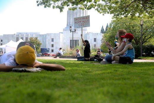 People sit on the grass and listen to speakers during the War on Racism rally at the Oregon State Capitol, in Salem, Oregon, on Saturday, July 11, 2020.