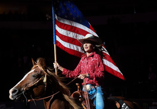 Gov. Kristi Noem presents the U.S. flag before the national anthem is played at the Professional Bull Riders competition on Saturday, July 11, 2020 at the Denny Sanford Premier Center in Sioux Falls, S.D.