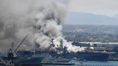 Smoke rises from the USS Bonhomme Richard at Naval Base San Diego ion Sunday.