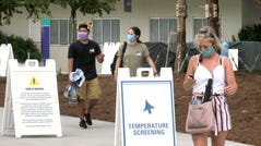 Guests wear masks as required as they arrive to attend the official reopening day of the Magic Kingdom at Walt Disney World in Lake Buena Vista, Fla., on July 11, 2020.
