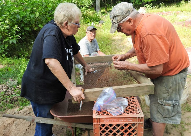 Sandy Pattison and Dallas Mauk look on as Mark Hersman examines an artifact found by Pattison while sifting soil through screens at a prehistoric people salvage dig site in eastern Coshocton County. Items found at the one-acre site includes arrowheads, flint chips and pottery shards.